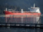 "A razor wire security fence floats in front of the STI Battery oil and chemical tanker during an emergency response exercise in Burrard Inlet at the Kinder Morgan Inc. Westridge Marine Terminal in Burnaby, British Columbia, Canada, on Wednesday, Sept. 19, 2018. A Canadian court's decision to nullify approval of the Trans Mountain Expansion Project will increase crude-by-rail transport in the near term and will likely have a ""negative impact on Canadian output growth in the longer term,"" the International Energy Agency said earlier this month. Photographer: Darryl Dyck/Bloomberg"