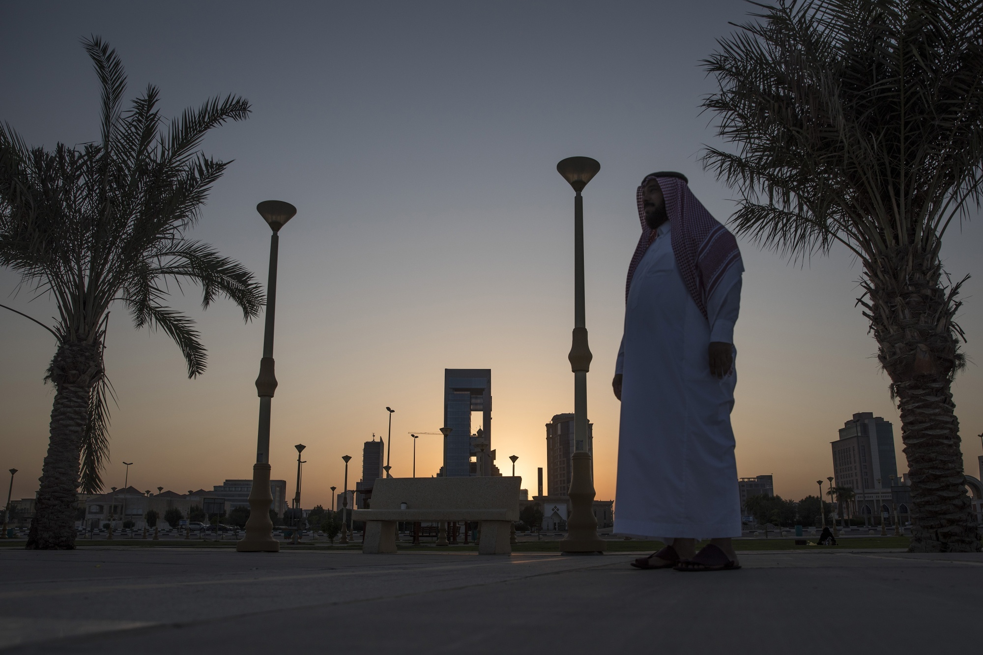 A man walks past palm trees lining the corniche promenade in Dhahran, Saudi Arabia, on Thursday, Oct. 4, 2018.
