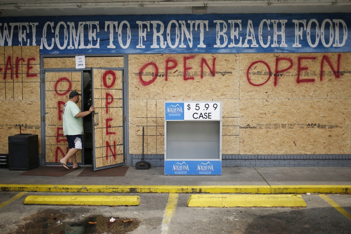 A customer enters a boarded up gas station in Panama City Beach, Florida Photographer: Luke Sharrett/Bloomberg