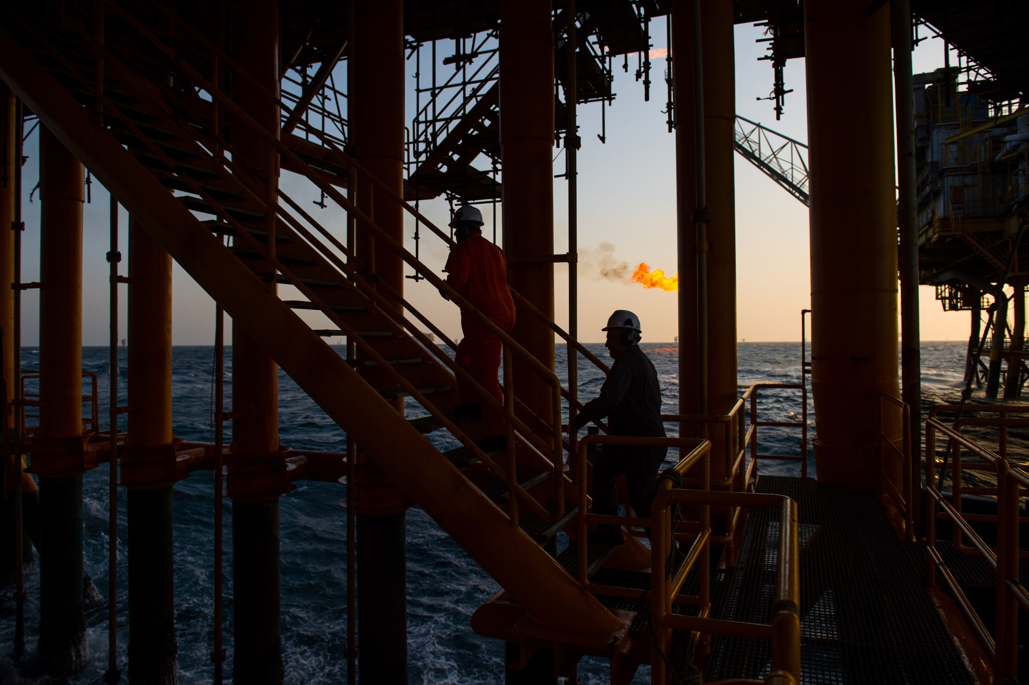 Workers climb stairs from a lower deck aboard an offshore oil platform in the Persian Gulf's Salman Oil Field, operated by the National Iranian Offshore Oil Co., near Lavan island, Iran, on Thursday, Jan. 5. 2017. Nov. 5 is the day when sweeping U.S. sanctions on Iran's energy and banking sectors go back into effect after Trump's decision in May to walk away from the six-nation deal with Iran that suspended them. Photographer: Ali Mohammadi/Bloomberg