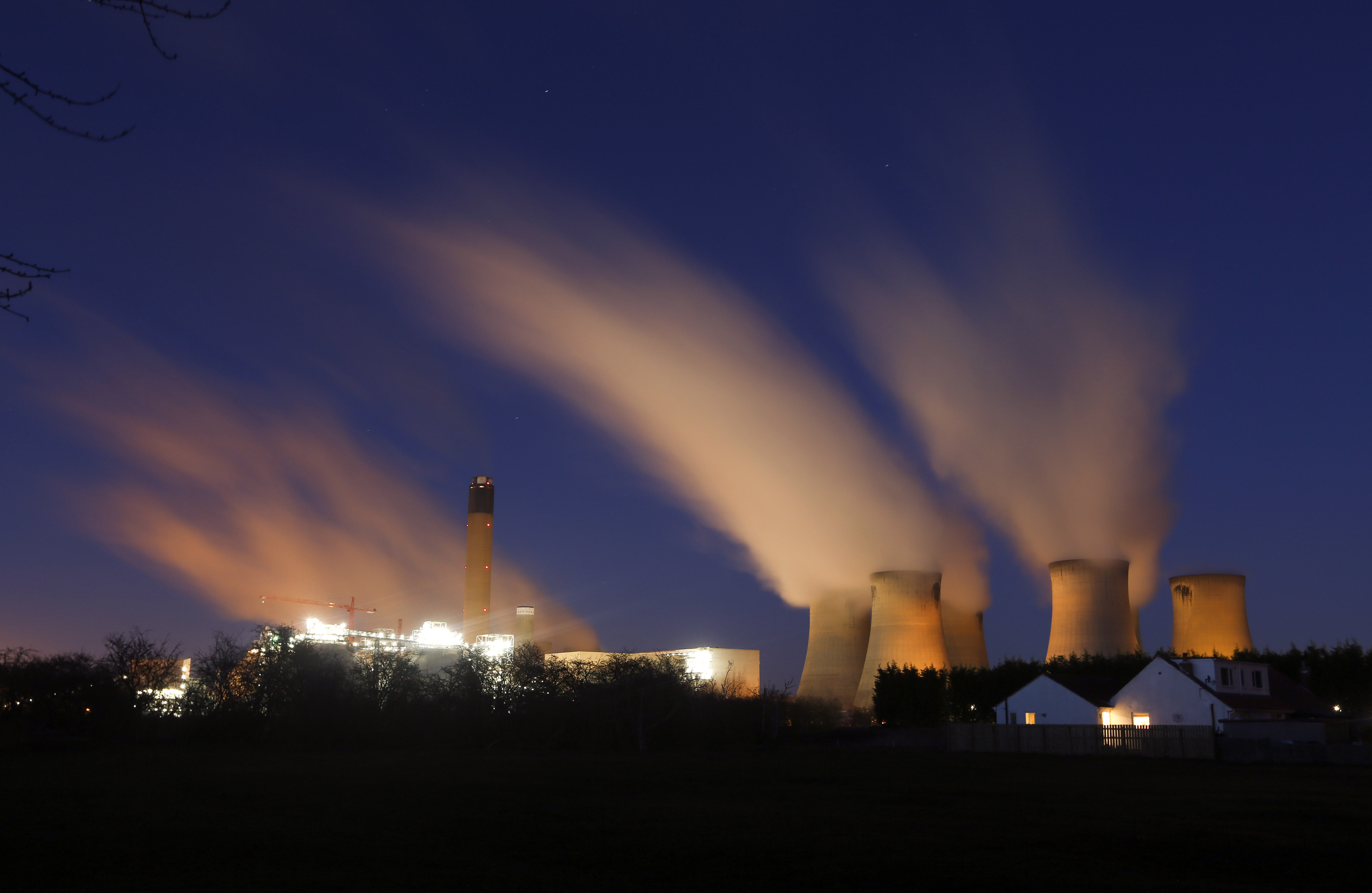 Vapour rises from cooling towers at Drax Power Station, operated by Drax Group Plc, at night in Selby, U.K. Photographer: Chris Ratcliffe/Bloomberg