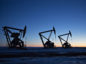 The silhouettes of pumpjacks are seen above oil wells in the Bakken Formation near Dickinson, North Dakota, U.S., on Wednesday, March 7, 2018.