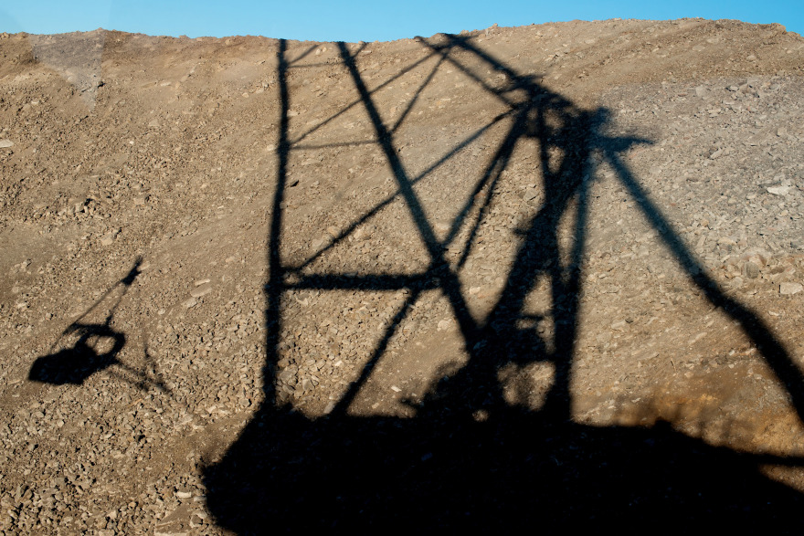 The shadow of a dragline excavator falls on oil shale during digging operations at Eesti Energia AS's open pit mine in Narva, Estonia. Photographer: Peter Kollanyi/Bloomberg