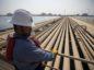 An employee looks out over oil transport pipelines on the Arabian Sea in Saudi Aramco's Ras Tanura oil refinery and oil terminal in Ras Tanura, Saudi Arabia. Photographer: Simon Dawson/Bloomberg