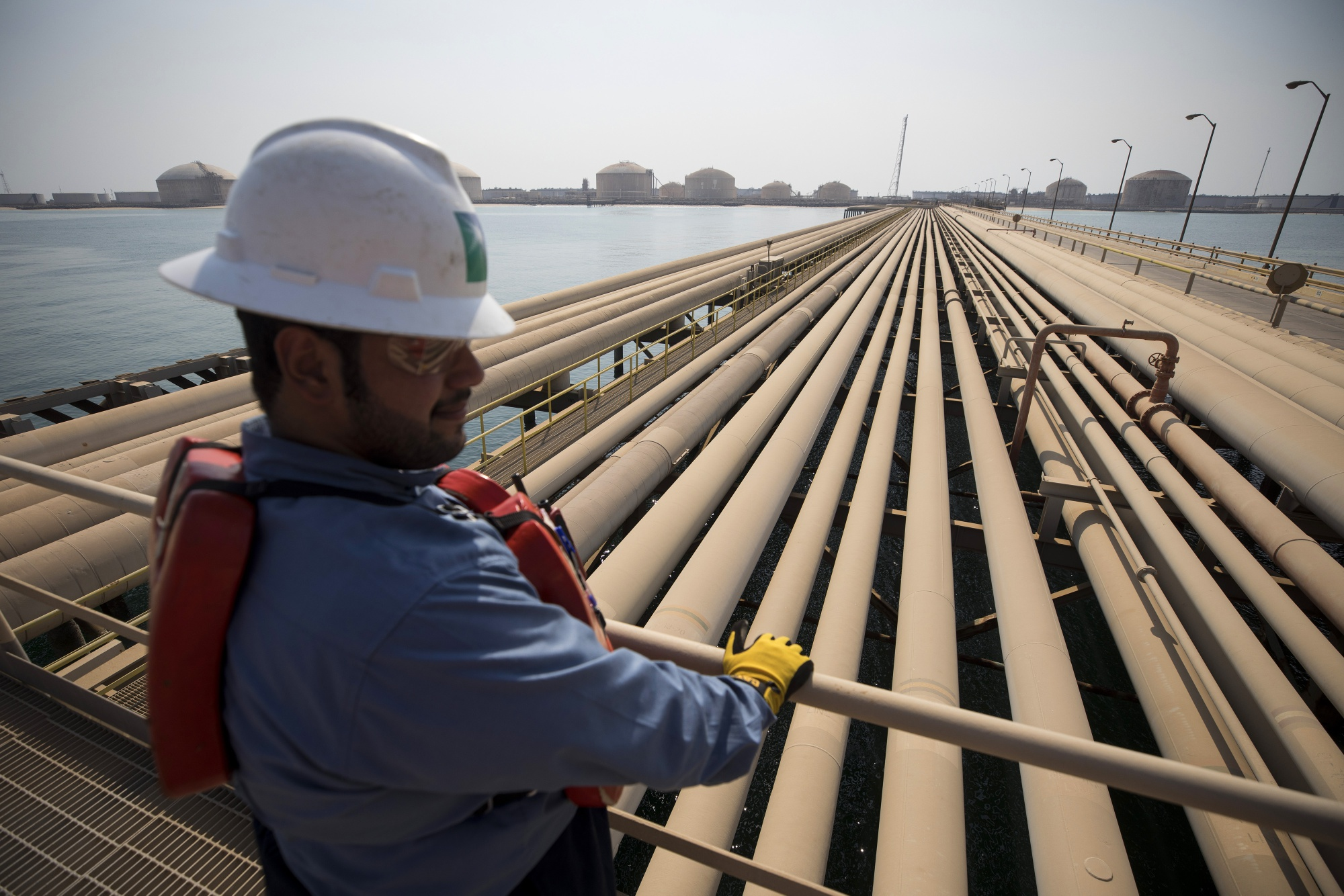 An employee looks out over oil transport pipelines on the Arabian Sea in Saudi Aramco's Ras Tanura oil refinery and oil terminal in Ras Tanura, Saudi Arabia. Photographer: Simon Dawson/Bloomberg