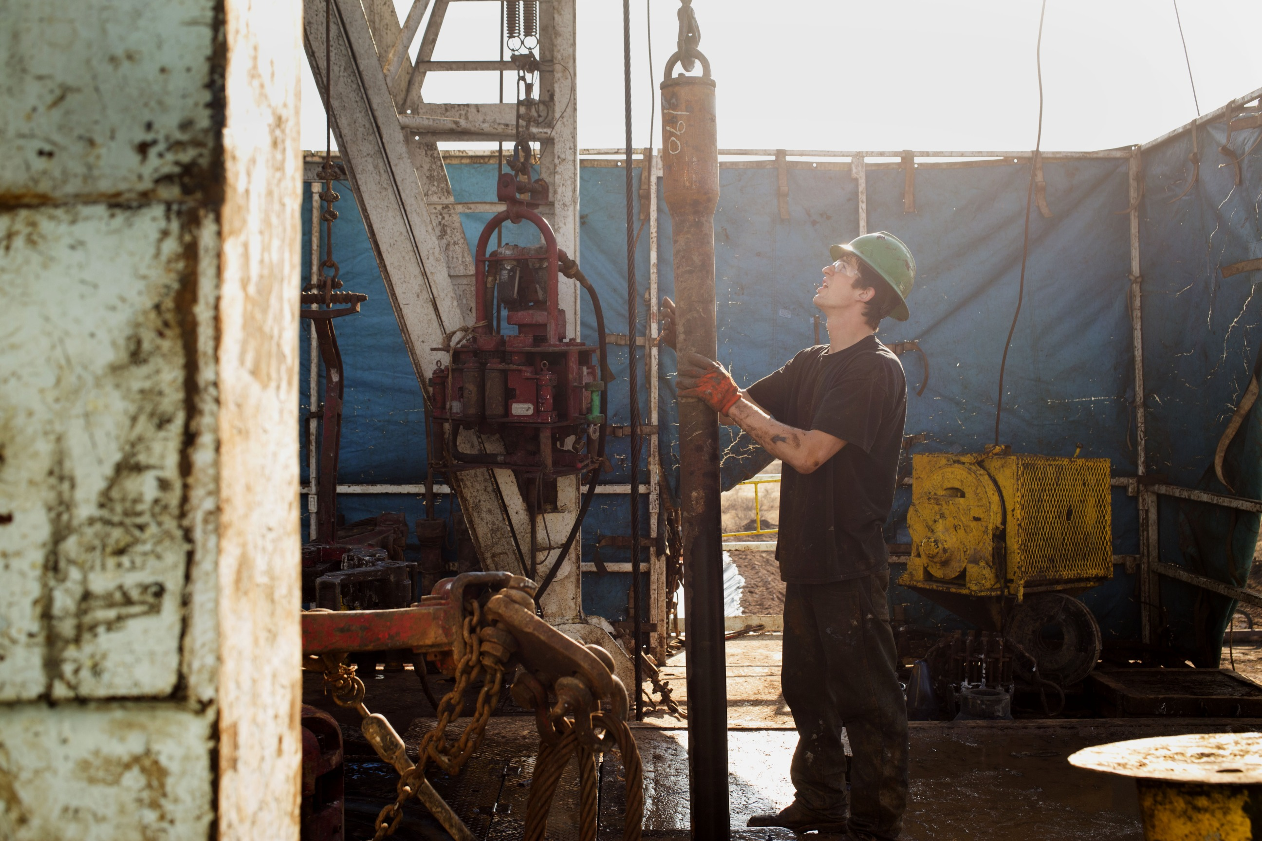 A worker checks the drilling rig before attaching it to the turntable on Endeavor Energy Resources LP's Big Dog Drilling Rig 22 in the Permian basin outside of Midland, Texas, U.S., on Friday, Dec. 12, 2014.  Photographer: Brittany Sowacke/Bloomberg