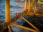 A worker looks out to sea from a low walkway aboard an offshore oil platform in the Persian Gulf's Salman Oil Field, operated by the National Iranian Offshore Oil Co., near Lavan island, Iran. Photographer: Ali Mohammadi/Bloomberg