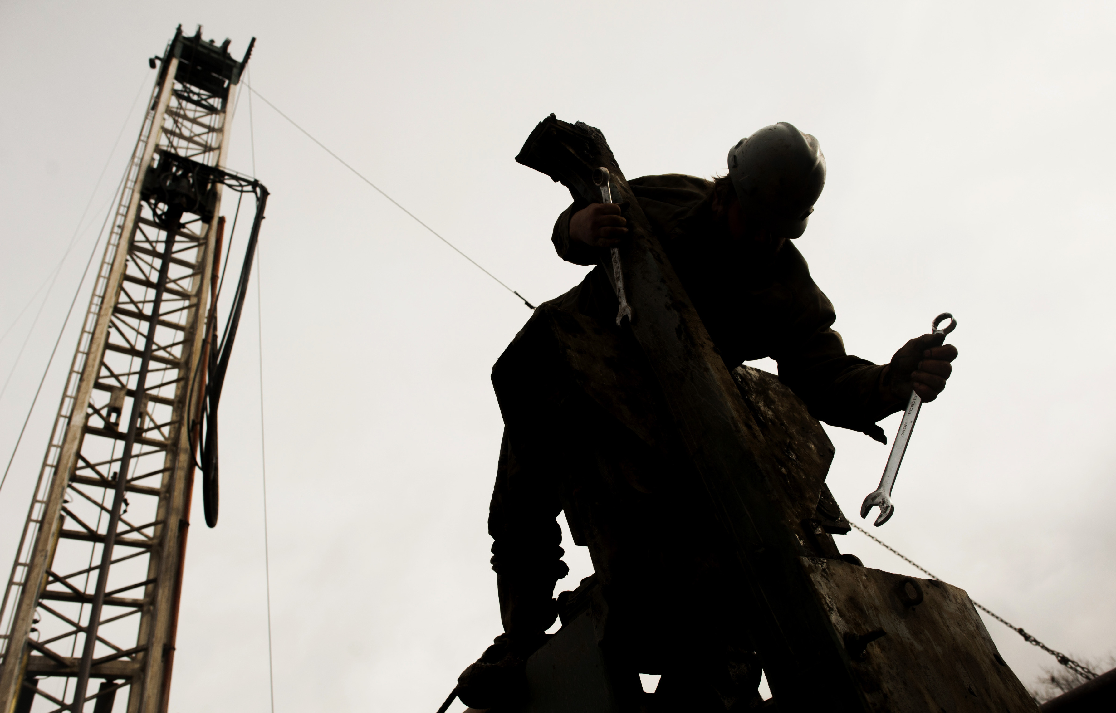 The silhouette of a rig hand is seen repairing the boom arm. Photographer: Ty Wright/Bloomberg