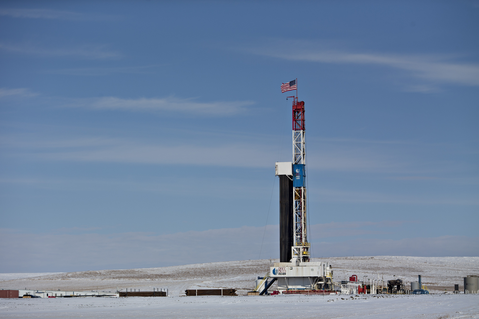 An American flag flies on top of a Unit Drilling Co. rig in the Bakken Formation outside Watford City, North Dakota, U.S., on Friday, March 9, 2018.  Photographer: Daniel Acker/Bloomberg
