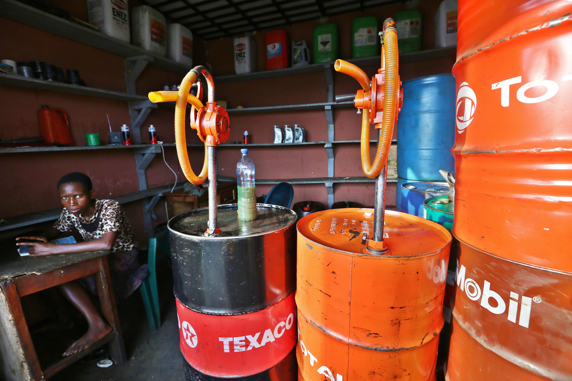 A street vendor waits for customers to buy his oil, delivered from old oil drums belonging to Texaco Inc., Exxon Mobile Corp, and Total SA, from a roadside store in Port Harcourt, Nigeria, on Wednesday, Jan. 13, 2016.  Photographer: George Osodi/Bloomberg