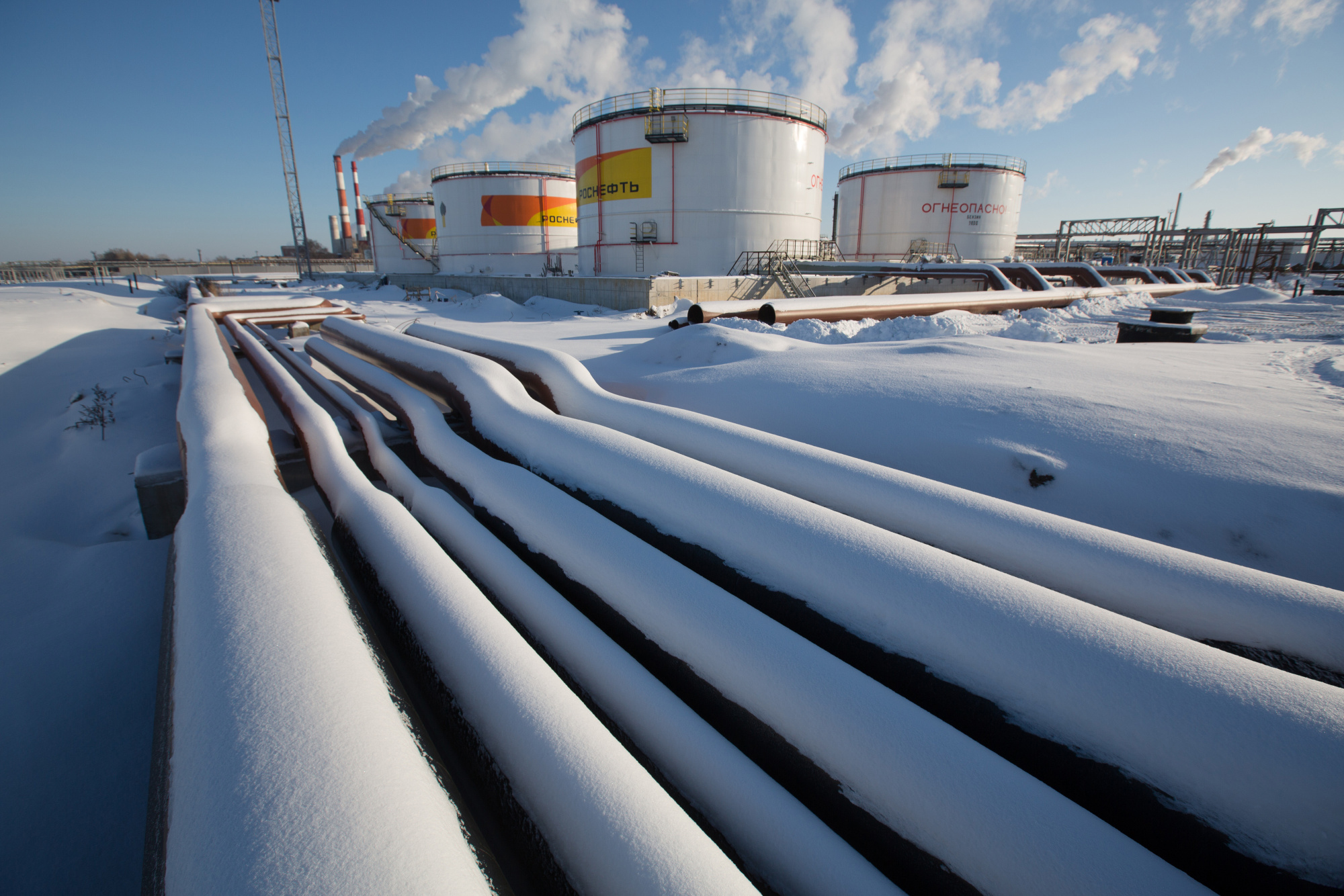 Oil pipelines and storage tanks stand in the snow at the Novokuibyshevsk oil storage plant, operated by Rosneft PJSC, in Novokuibyshevsk, Samara region, Russia, on Thursday, Dec. 22, 2016.  Photographer: Andrey Rudakov/Bloomberg