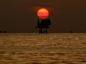 An offshore oil platform and wells are silhouetted by the setting sun in the Gulf of Mexico off the coast of Louisiana, U.S., on Thursday, July 15, 2010. Photographer: Derick E. Hingle