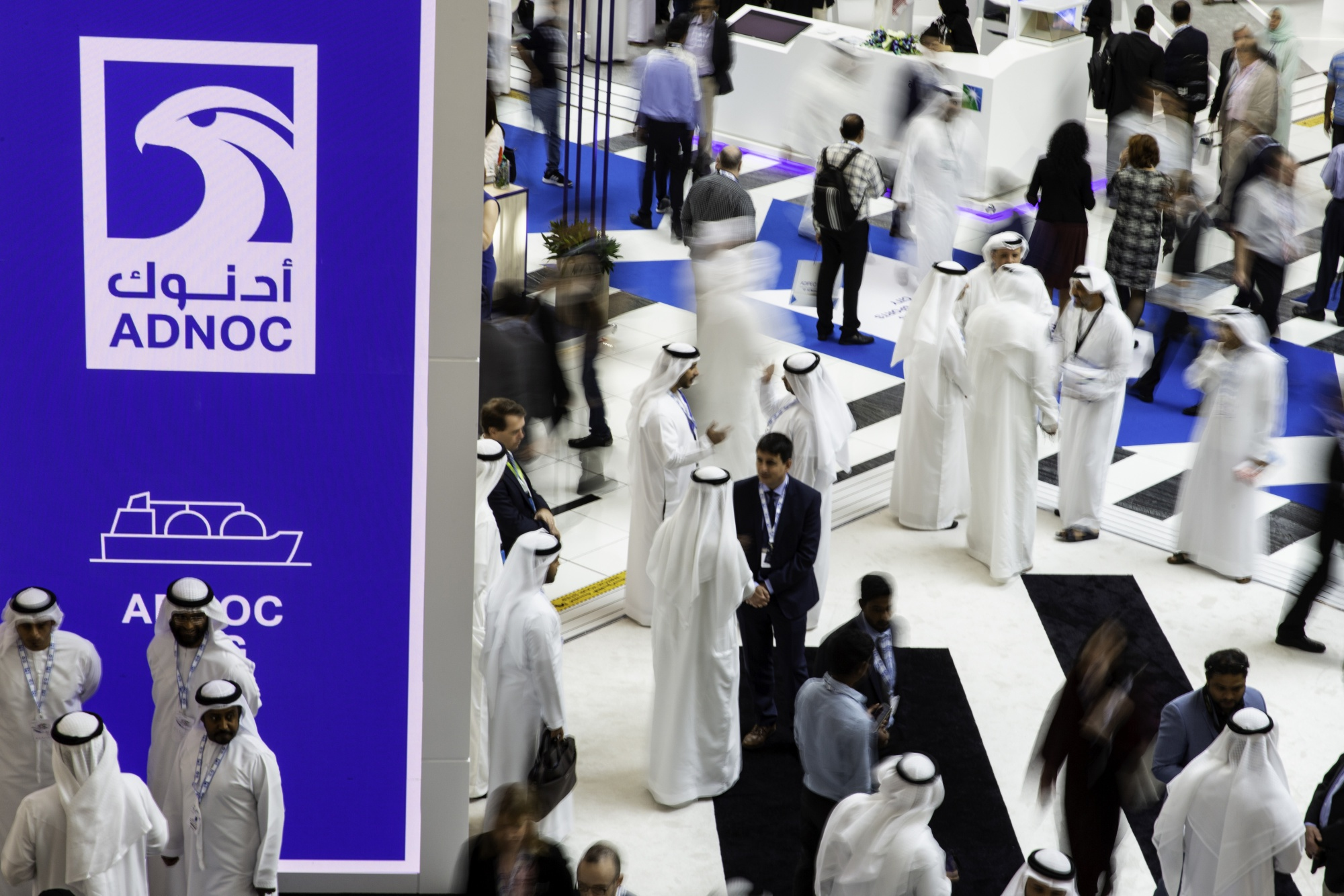 Delegates pass the Abu Dhabi National Oil Co. (ADNOC) display during the Abu Dhabi International Petroleum Exhibition & Conference (ADIPEC) in Abu Dhabi, United Arab Emirates, on Tuesday, Nov. 13, 2018. OPEC's secretary-general, energy ministers from Saudi Arabia to Russia, CEOs at oil majors from Total SA, BP Plc and Eni SpA, and officials from Middle Eastern energy giants such as Abu Dhabi's Adnoc have gathered to sign deals and discuss oil, gas, refining and petrochemical issues. Photographer: Christopher Pike/Bloomberg