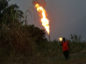 A man walks through foliage as gas flares burn in Idu, Rivers State, Nigeria. Photographer: George Osodi/Bloomberg