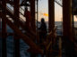 Workers climb stairs from a lower deck aboard an offshore oil platform, Photographer: Ali Mohammadi/Bloomberg