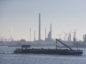 A barge sails past storage tanks and chimneys at the Q8 Europort refinery, operated by Kuwait Petroleum Corp., in the Port of Rotterdam in Rotterdam, Netherlands. Photographer: Jasper Juinen/Bloomberg