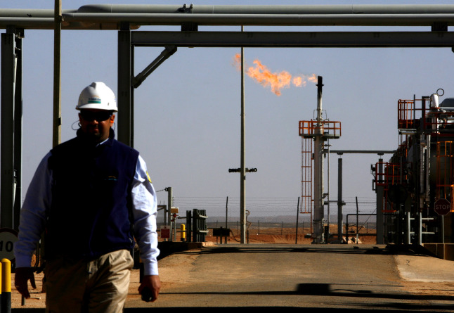 An employee walks in front of a gas flare at the In Salah Gas (ISG) Krechba Project, run by Sonatrach, British Petroleum (BP), and StatoilHydro, in the Sahara desert near In Salah, Algeria, on Sunday, Dec. 14, 2008.  Photographer: ADAM BERRY/Bloomberg