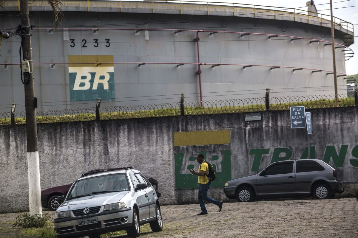 A man walks past an oil storage tank at the Petrobras Transporte SA (Transpetro) sea terminal in Sao Sebastiao, Sao Paulo state, Brazil, on Wednesday, Dec. 19, 2018.  Photographer: Dado Galdieri/Bloomberg