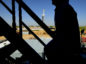 The silhouette of a contractor is seen walking up stairs at an Anadarko Petroleum Corp. oil rig site in Fort Lupton, Colorado. Photographer: Jamie Schwaberow/Bloomberg