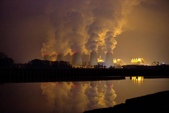 Chimneys emit vapor at Jaenschwalde lignite power plant, operated Vattenfall AB, at dusk in Peitz, Germany, on Tuesday, Dec. 15, 2015.  Photographer: Krisztian Bocsi/Bloomberg