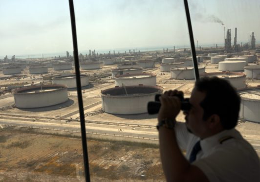 An employee uses binoculars to look out towards the Arabian Sea in the Port Control Center at Saudi Aramco's Ras Tanura oil refinery and terminal in Ras Tanura, Saudi Arabia, on Monday, Oct. 1, 2018.  Photographer: Simon Dawson/Bloomberg
