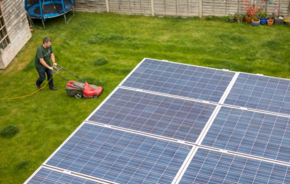 Hill mows his lawn in view of his solar panels.  Photographer: Chris Ratcliffe/Bloomberg