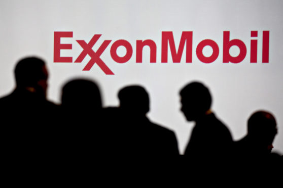 Attendees stand near Exxon Mobil Corp. signage during the World Gas Conference in Washington, D.C., U.S, on Tuesday, June 26, 2018. The 27th World Gas Conference, themed Fueling the Future, is held every three years in the country holding the Presidency of the International Gas Union (IGU). Photographer: Andrew Harrer/Bloomberg