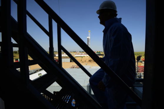 The silhouette of a contractor is seen walking up stairs at an Anadarko Petroleum Corp. oil rig site in Fort Lupton, Colorado, U.S., on Tuesday, Aug. 12, 2014.  Photographer: Jamie Schwaberow/Bloomberg