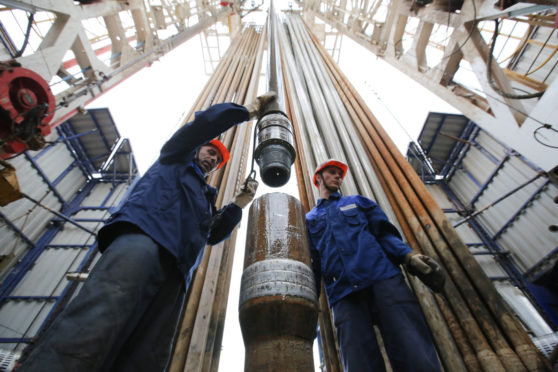 Workers secure drilling pipe sections on an oil drilling tower operated by Tatneft OAO near Almetyevsk, Russia, on Friday, July 31, 2015. Photographer: Andrey Rudakov