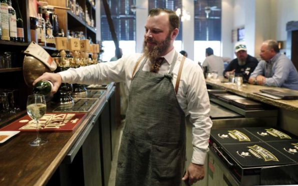 Bartender Sean Stapleton serves drinks to the regulars during happy hour at The Refuge Bar and Bistro Tuesday, Jun. 4, 2019 in The Woodlands, TX. Local area businesses are concerned about the possibility of Anadarko employees and the headquarters relocating, and The Refuge sees quite of few of those employees frequent the bar.