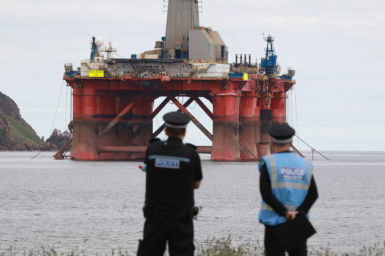 Police look on as activists continue their protest on an oil rig in Cromarty Firth.