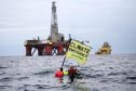 Greenpeace campaigner Sarah North holds a banner whilst floating in front of BP rig on day 11 of the protest in the North Sea.