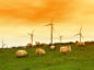 Modern windmill in the dusk with sheep on Scottish fields