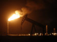 The silhouette of an electric oil pump jack is seen near a flare at night in the oil fields surrounding Midland, Texas. Photographer: Luke Sharrett/Bloomberg