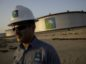 An employee visits the site of crude oil storage tanks at the Juaymah tank farm at Saudi Aramco's Ras Tanura oil refinery and oil terminal in Ras Tanura, Saudi Arabia.
