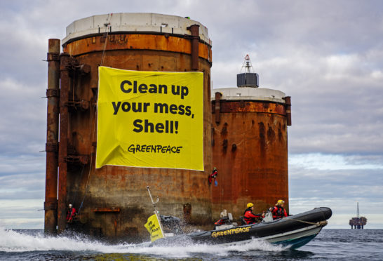 Climbers, supported by the Greenpeace ship Rainbow Warrior, scaled Brent Alpha and Bravo and hung banners saying, 'Shell, clean up your mess!' and 'Stop Ocean Pollution'. Pic: Greenpeace
