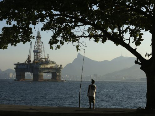 A man fishes in Guanabara Bay while an oil drilling platform floats in the background near Niteroi, Brazil, on Monday, April 20, 2015. Petroleo Brasileiro SA (Petrobras), the state-controlled oil producer at the center of an ever-widening corruption investigation, plans to release its audited third-quarter and 2014 results after markets close on April 22, 2015, ending a five-month wait for investors. Photographer: Dado Galdieri/Bloomberg